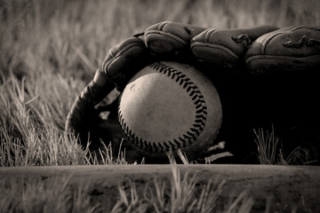 Vintage baseball sport graphic image with closeup of ball and glove in field after game.