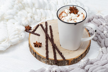White cup of hot cocoa with marshmallows and chocolate sticks on wooden stand. Selective focus.