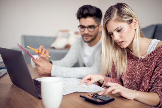 Modern young  couple paying bills online from home
