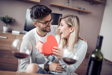 Young couple with present at home