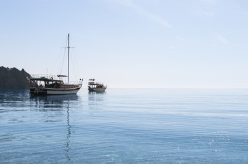 Small yacht and boat in the blue calm sea under cloudless sky in sunny morning; Sailboat with folded sails; Reflection of ships in calm water; Seascape with two boats