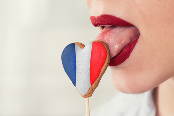 Closeup photo of the woman lips and cookie hearts with flag of France