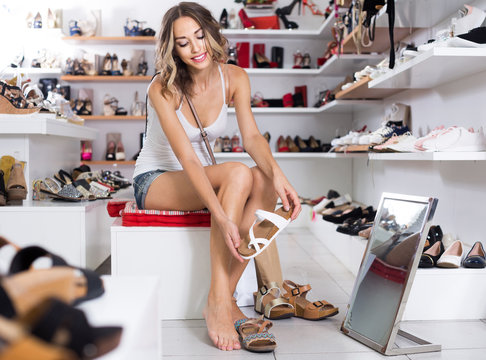 Woman 20-23 years old is trying on summer shoes in boutique.