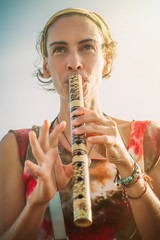 Young woman playing bamboo flute on summer day