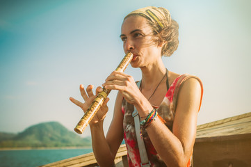 Young woman sitting on boat and playing bamboo flute