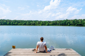 man sitting with laptop and looking on lake. working at vacation. summer time concept