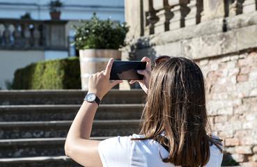 The girl photographs a mobile phone in the castle garden