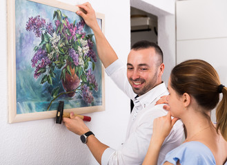 Man is hanging the picture on the wall together with his wife