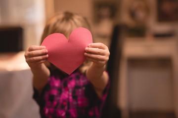 Girl holding heart shape decoration