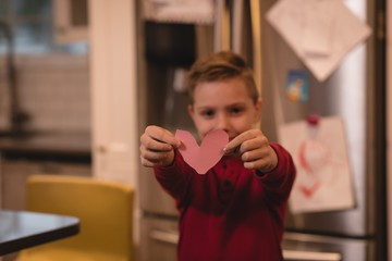 Boy holding heart shape decoration
