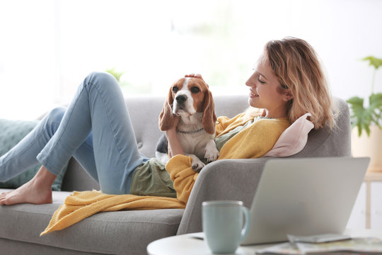 Young woman with her dog on sofa at home