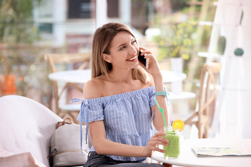 Young woman using mobile phone while drinking tasty healthy smoothie at table, indoors