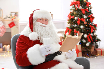 Authentic Santa Claus with glass of milk reading book indoors