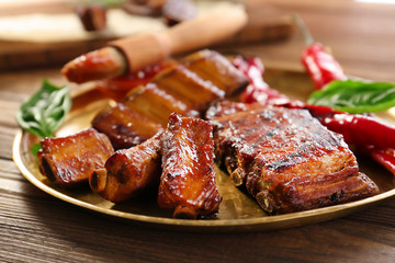 Plate with delicious grilled ribs on table