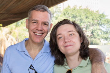 Grey haired dad and young adult son smiling. Father Day. Concept of bonding, enjoyment, fatherhood.