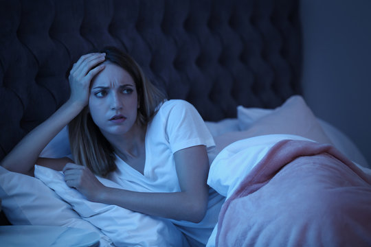Young woman suffering from insomnia in bed at night. Sleeping problems