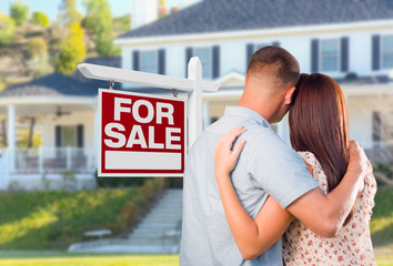 Military Couple Looking At House with For Sale Real Estate Sign In Front