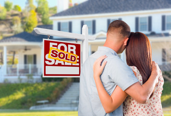 Military Couple Looking At House with Sold For Sale Real Estate Sign In Front