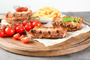 Wall Mural - Wooden board with delicious grilled ribs and vegetables on table