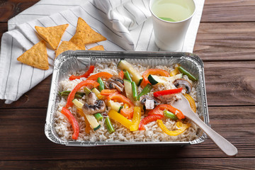 Foil container with tasty brown rice and vegetables on table
