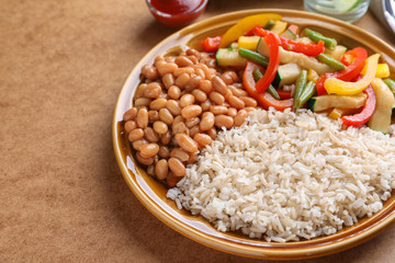 Plate with brown rice with beans and vegetables on table