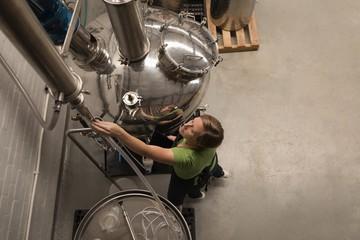 Female worker checking machine of distillery