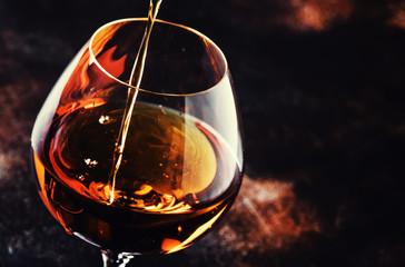 Cognac Pour Into Glass, Vintage Brown Background, Selective Focus