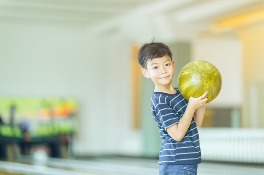 boy in bowling alley cheering and smiling