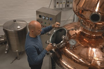 Male worker checking machine of distillery