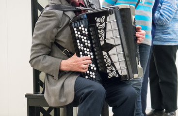 Elderly retired grandfather playing on accordion.