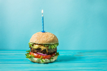 Homemade burger barbeque sandwich with beef and lit candle for birthday party on blue background. Concept holiday