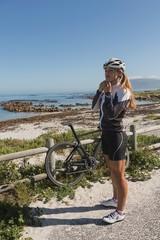 Female biker wearing her helmet near beach