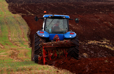 A farmer uses a tractor to plough a field near city of Veles