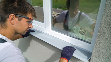 Man worker in safety glasses and protective gloves installing metal sill on external PVC window frame. Window sill installation process. Technology, exterior design, building concept