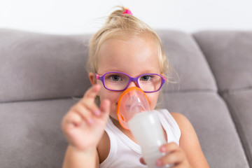 Little girl is taking inhalation therapy by the mask of a nebuliser