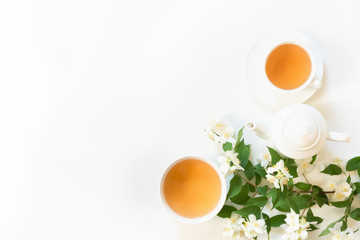 Green jasmin tea and jasmine flowers, cup of green tea on white. Top view. Teatime. Copy space.