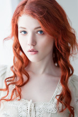 Tender retro portrait of a young beautiful dreamy redhead woman.