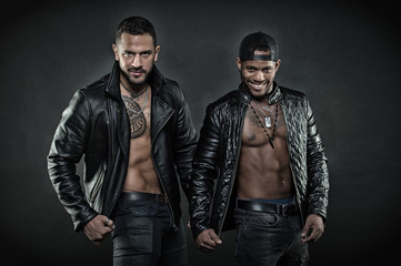 Two men in leather jackets on black background. Brutal Hispanic man with geometrical tattoo. African man with happy smile wearing cap backwards. Models with sexy muscular bodies, fitness concept