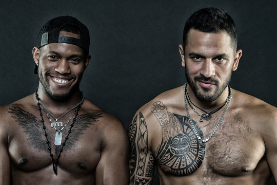 Fashion models smiling African man and tattooed Caucasian guy. Bodybuilders on black background. Sportsmen with sexy torsos, body care and fitness concept. Fashion models in trendy accessories