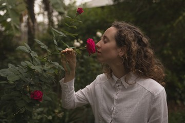 Woman smelling red rose in the garden