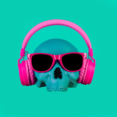 Skull in pink headphones and glasses on a turquoise background. Fashion minimal art.