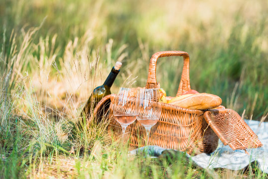 wine bottle, basket with loaves on green grass at picnic