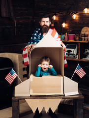 international friendship, freedom and people concept - happy family with american flag at paper rocket.
