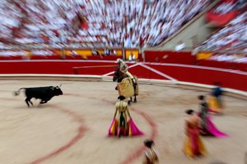 A picador (mounted bullfighter) prepares to drive a lance into a charging bull during a bullfight at the San Fermin festival in Pamplona
