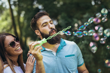 Charming young couple sitting on bench in the park and blowing bubbles.