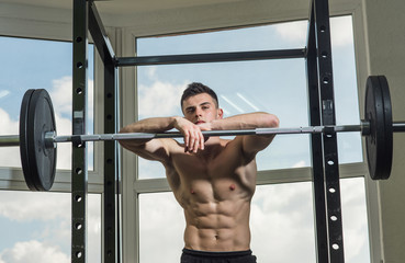 Sportsman, athlete with muscles looks attractive. Sport and gym concept. Man with torso, muscular macho lean on barbell, window on background. Man with nude torso in gym enjoy his sporty lifestyle