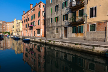 Colourful buildings reflect in a still canal, Venice, Italy