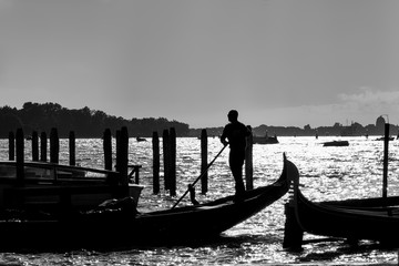 Silhouette of gondolier and gondolas on grand canal; Venice, Italy