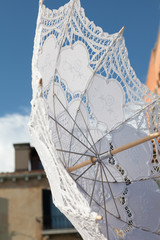 White parasol for sale by a Venice merchant.