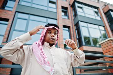 Middle Eastern arab man posed on street against modern building.
